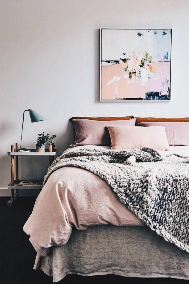 Chunky Gray Blanket With Gray Skirting And Pale Pink Pillows And Sheets