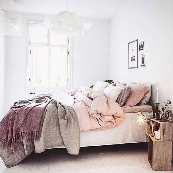 A Shaded Array Of Mauve, Gray, And Light Pink Blankets And Pillows
