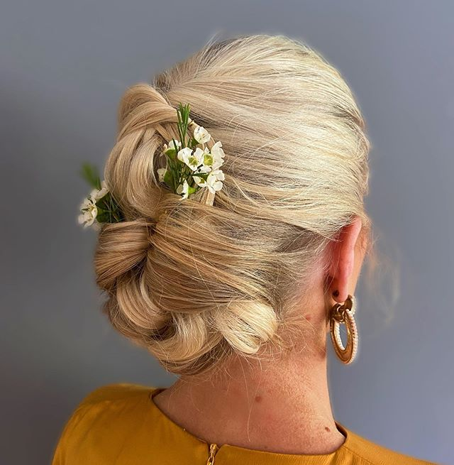 Artfully Twisted Sleek Updo With Floral Accents